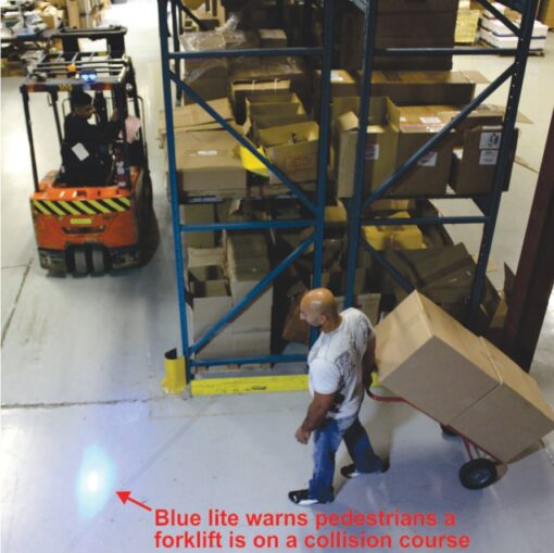 A forklift in reverse with a blue light on the floor to warn pedestrians.